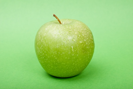 Ripe green apple with water drops on green background photo