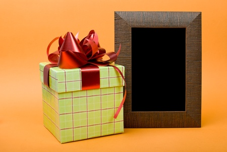 Wood photo frame and green gift box with red ribbon on orange background. photo