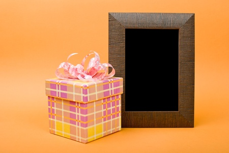 Wood photo frame and yellow gift box with pink ribbon on orange background. photo