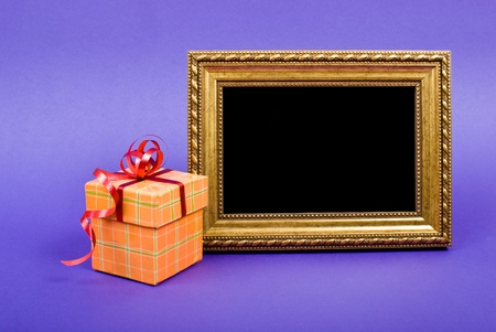 Gold photo frame and orange gift box with red ribbon on blue background. photo
