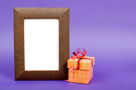Wooden photo frame and orange gift box with red ribbon on blue background. photo