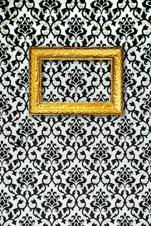 Gold frame on a black and white wallpaper Stock Photo - 13231015