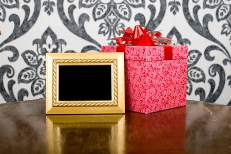 Golden photo frame and present box on table Stock Photo