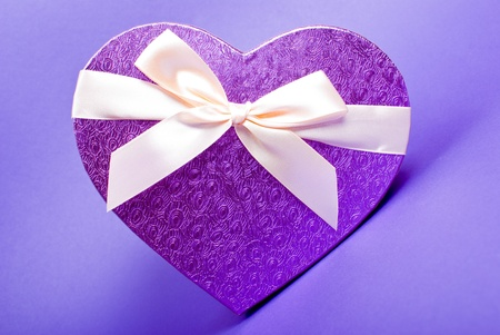 Single heart gift box with ribbon on blue background. photo