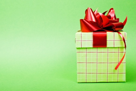 Single green gift box with red ribbon on green background. photo