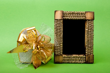 Wood photo frame and heart gift box with ribbon on green background. photo