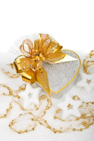 Christmas silver heart gift box with golden ribbon in snow on a white background. photo