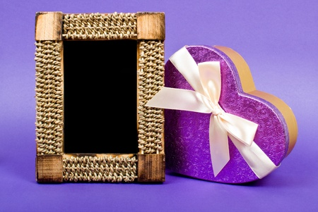 Wooden photo frame and heart gift box with ribbon on blue background. photo