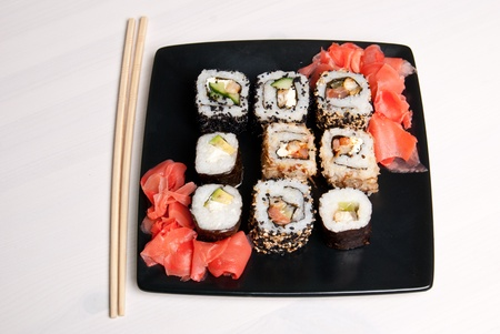 Sushi on a black plate on white table. Stock Photo - 13230941