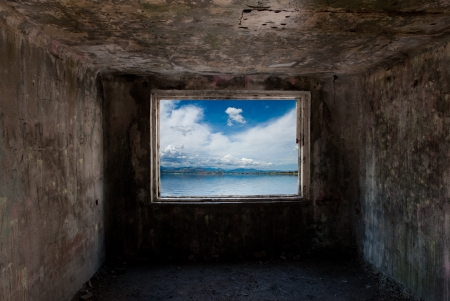 Dark old room with window with sea behind him photo