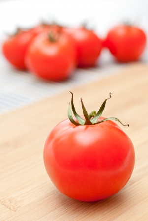 Fresh ripe tomatoes on an chopping board photo