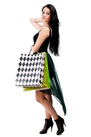 Young happy woman in dress with colorful shopping bags on a white background photo