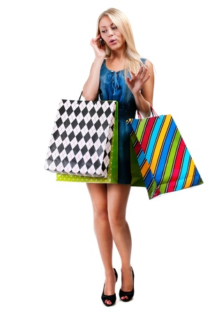Young woman with shopping bags and mobile phone on a white background photo