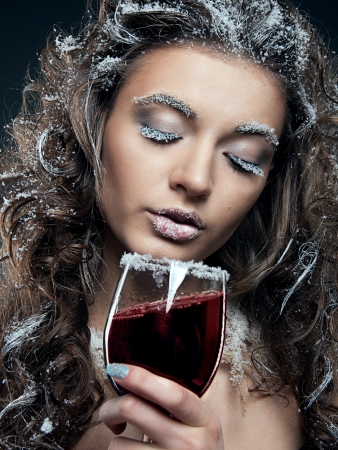 Portrait of young woman with snow make-up with a glass of wine. Christmas snow queen photo