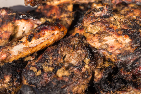Closeup of grilled  spicy jerk chicken cooked over wood  fire.
