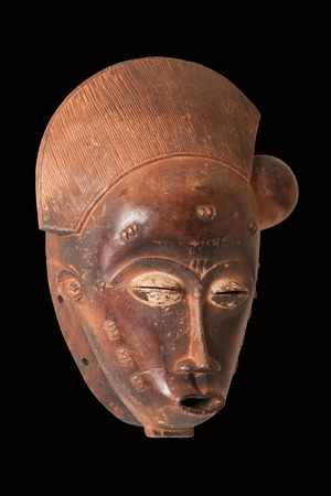 Baule female mask from Ivory CoastAfrica, carved in wood with pigmentkaolin patina; small splits, scrapes and cracks attest to its ageuse.
