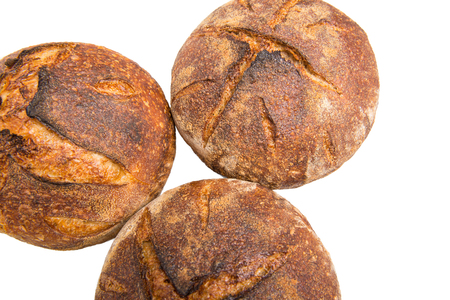 Fresh baked loaves of round artisan sourdough bread isolated on a white background.