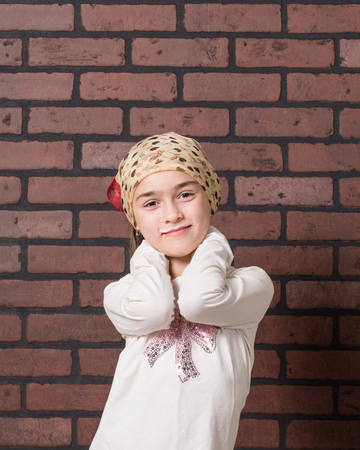 Young girl with a milk mustache gesturing expressively in front of a brick wall background. Imagens