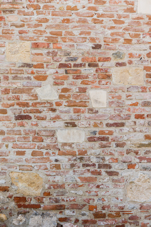 Old brick and stone wall in grey tones with thick grout and very rough, irregular surface. Stock Photo