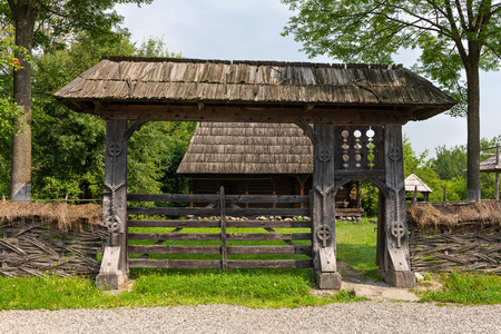 Traditional handmade wooden carved gate from Maramures region in northern Romania. Фото со стока