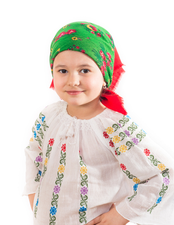Closeup of a young girl with head dressed in traditional costume. Romanian folklore. Posing in a studio on a white background.