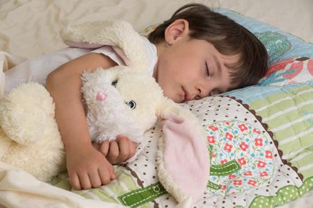 Girl sleeping with bunny gift on the Easter holidays.