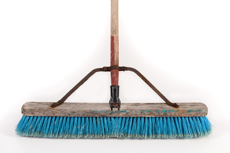 Dirty polypropylene push broom resting on a wall isolated on white.