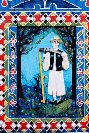 Naïve carved and painted plaque painting on cemetery cross describing the person that is buried as well as scenes from hisher live, location Merry Cemetery,  Maramures County, Romania.