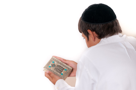 Jewish boy reading his Torah or prayer book isolated on white.