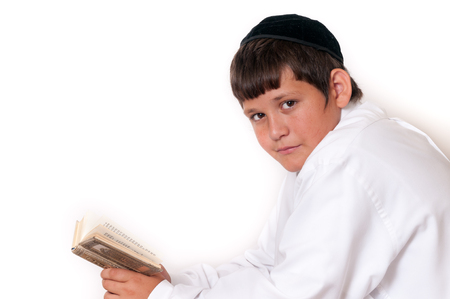 Jewish boy looks towards the camera while praying. Isolated on white.