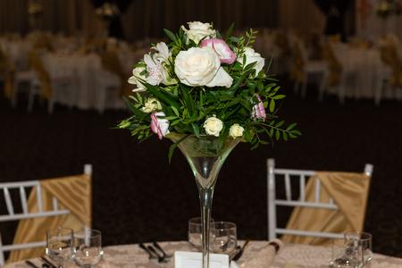 Floral centerpiece at luxury, elegant wedding reception table arrangement in banquet hall.