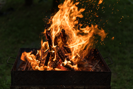 Close-up of blazing fire in BBQ grill at evening.