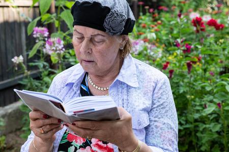 Older Jewish woman wearing jewelry reads her prayer book in backyard garden.