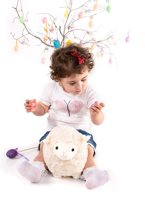 Toddler with Easter eggs hugs Easter lamb plush toy, isolated on white. Stock Photo