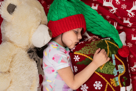 Sleeping girl at home at Christmas time with large Teddy bear plush toy. New Year winter holiday concept. Stock Photo