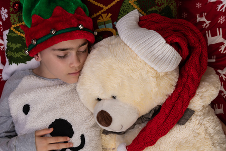 Sleeping girl at home at Christmas time with large Teddy bear plush toy. New Year winter holiday concept. 版權商用圖片