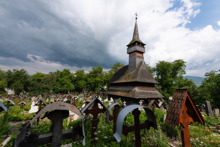 Ieud Hill Church and its graveyard, the oldest wood church in Maramures, Romania under dramatic sky. Stock Photo