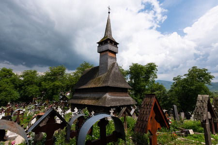 Ieud Hill Church and its graveyard, the oldest wood church in Maramures, Romania under dramatic sky. 免版税图像