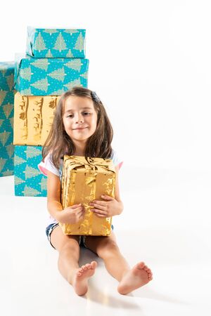 Cheerful young girl with stack of big gift boxes isolated on white with copy space. 写真素材