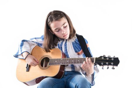 Niña preadolescente tocando su guitarra aislada sobre fondo blanco.