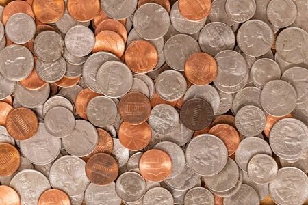 Large pile of various United States coins closeup background.