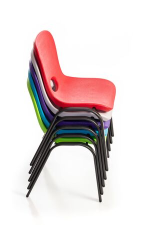 Plastic chairs for children of diverse colors stacked up on a white background, side view.