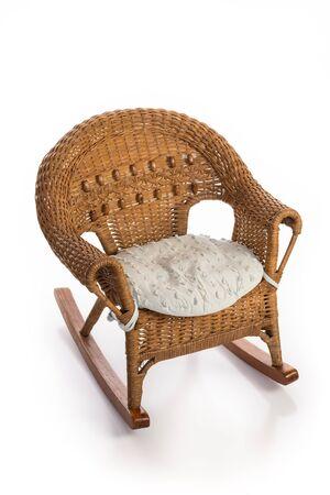 Chaise enfant à bascule en osier rustique avec un coussin de siège isolé sur blanc.