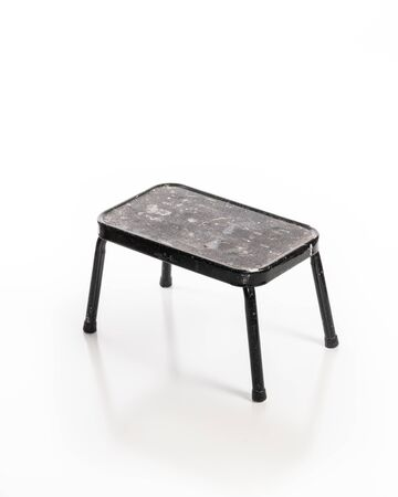 Used step stool used in renovation or contruction work isolated on white background.