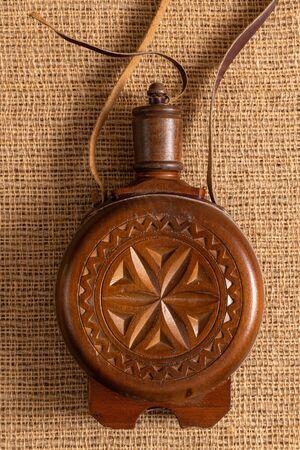 Ancien flacon traditionnel ou récipient à bouteille recouvert de bois sculpté pour conserver l'eau ou l'alcool.