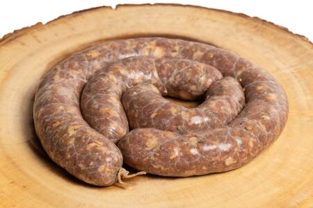 Raw homemade stuffed pork sausages isolated on a woodboard.