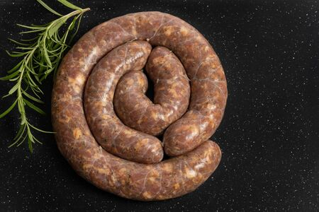Raw homemade stuffed pork sausages and rosemarie isolated on a black background.