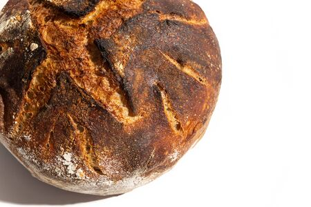 Close up of freshly baked artisan sourdough bread loaf isolated on white.