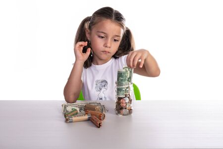 Girl playing and counting money from her glass piggy bank with copy space. Concept for business or teaching children for saving money.