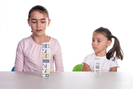 Two young girls of different ages playing with dominoes, concept of teamwork or unjust competition